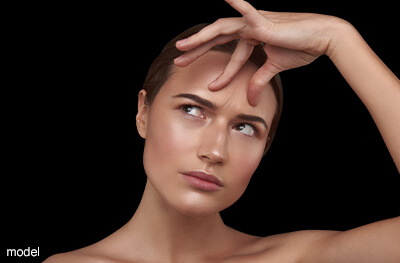 Model pinching lines between brow.